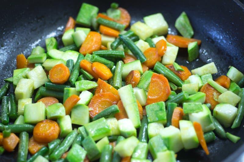 Gesneden die groenten, in boter in een pan worden gebraden stock afbeelding