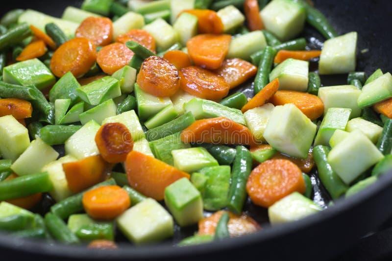 Gesneden die groenten, in boter in een pan worden gebraden wanneer het koken royalty-vrije stock afbeeldingen