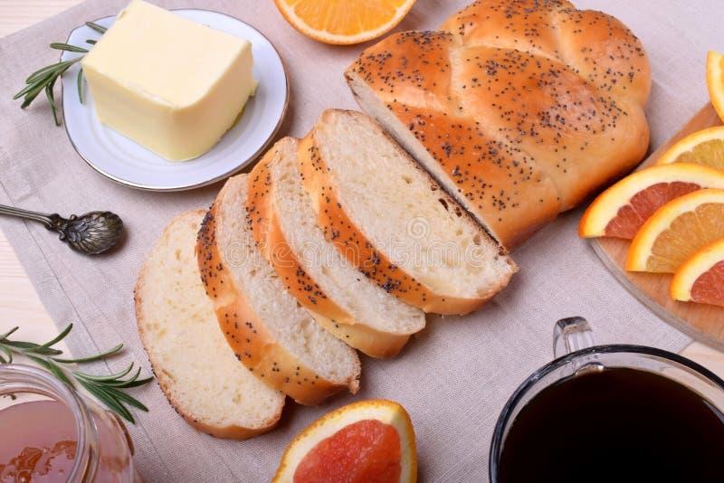 Gesneden die tarwebrood door boter en sinaasappel wordt omringd royalty-vrije stock fotografie