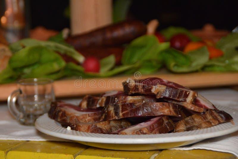 Gesneden drogend varkensvleesvlees op verfraaide lijst binnenlandse stijl in Balkan stock foto