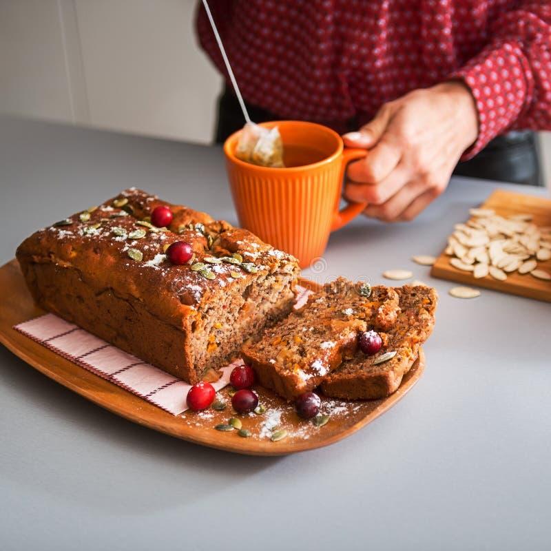 Gesneden eigengemaakt brood van pompoenbrood, de handen van de vrouw en thee stock foto's