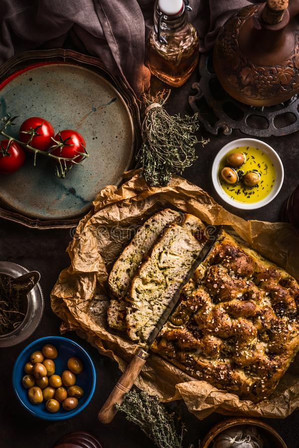 Gesneden eigengemaakte focacciabrood en mes met olijfolie en olijven op rustieke lijst, hoogste mening Italiaans voedselconcept stock afbeelding