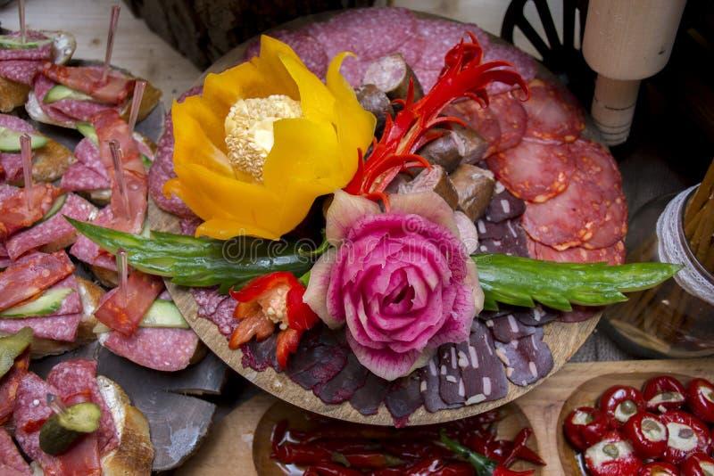 Gesneden geassorteerde genezen die vlees en worsten met gesneden bloemen van groenten wordt verfraaid stock foto's