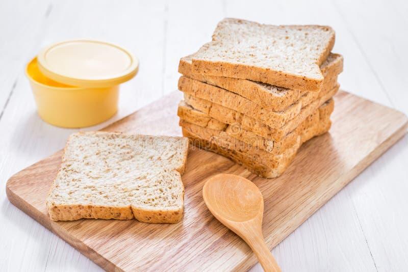 Gesneden geheel tarwebrood met boter op witte houten lijst stock fotografie