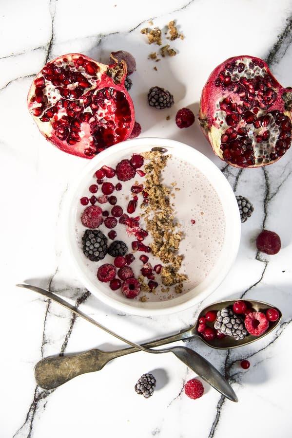 Gesneden granaatappel en eigengemaakte verse yoghurt met bosvruchten en graangewas Witte marmeren patroonachtergrond stock foto