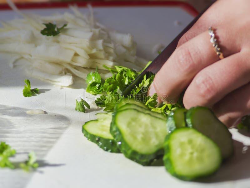 Gesneden groene peterselie en komkommer op witte lijst stock afbeeldingen