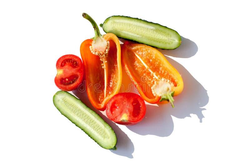 Gesneden Groentenkomkommers, Groene paprika's en Tomaten rode groene geeloranje in waterdalingen op witte achtergrond Geïsoleerde royalty-vrije stock fotografie