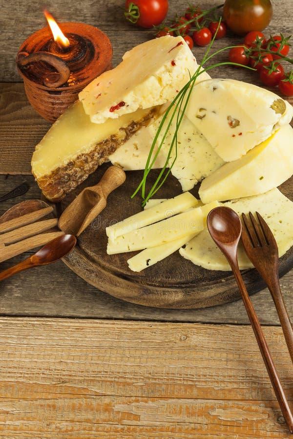Gesneden harde kaas op de keukenraad Productie van kazen op het landbouwbedrijf Verschillende types van eigengemaakte kaas royalty-vrije stock afbeeldingen