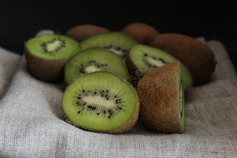 Gesneden kiwi dicht omhoog groen fruit, donkere achtergrond stock fotografie