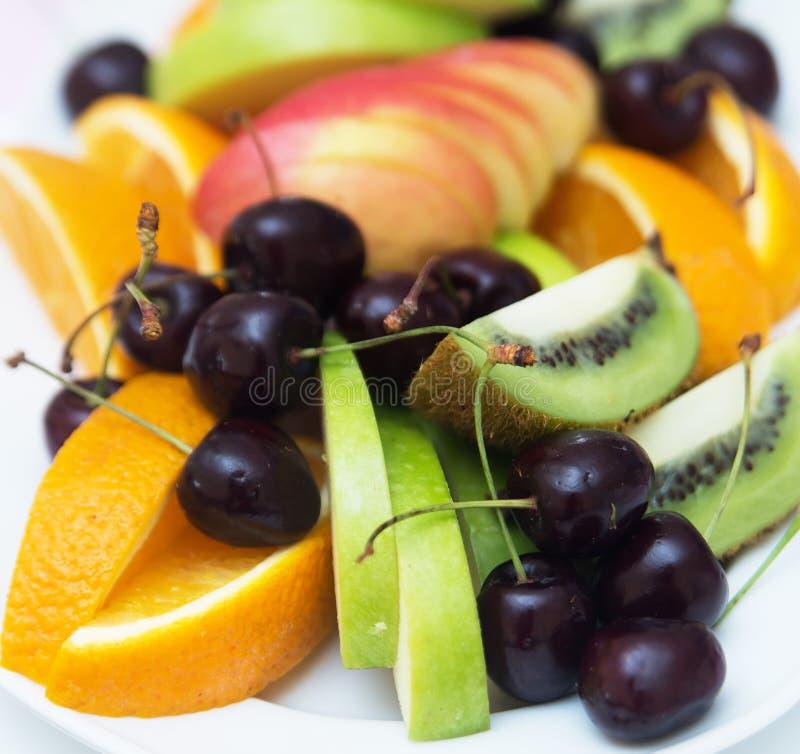 Gesneden kiwi met kers en sinaasappel en appel Vruchten royalty-vrije stock foto