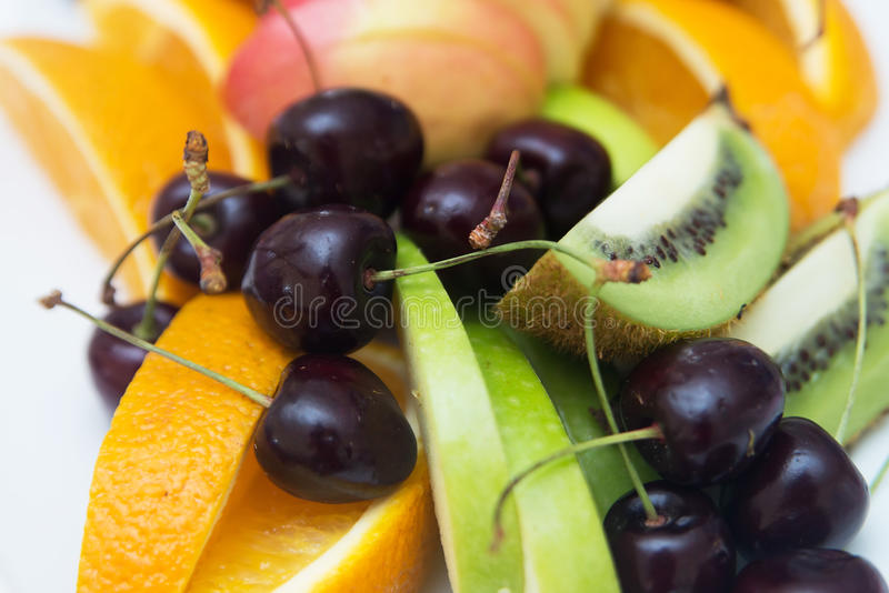 Gesneden kiwi met kers en sinaasappel en appel Vruchten royalty-vrije stock fotografie