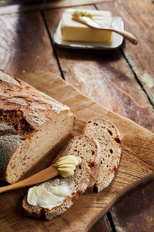 Gesneden knapperig brood van vers roggebrood met boter stock afbeelding