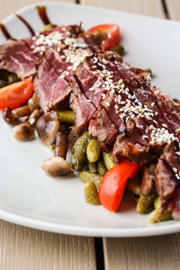 Gesneden middelgroot zeldzaam Braadstukrundvlees met groenten in het zuur, kersentomaten, paddestoelen op een witte plaat op hout stock foto's