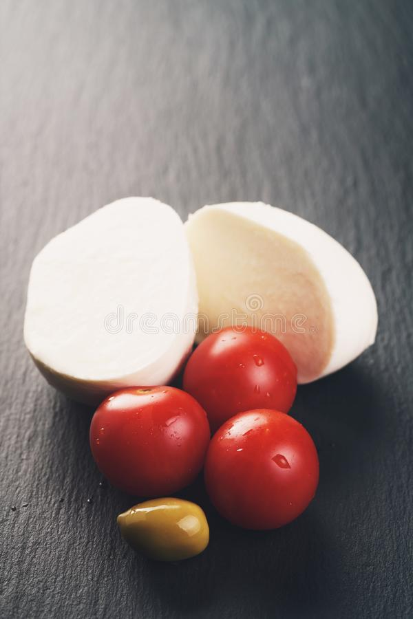 Gesneden mozarellabal met tomaat en olijven op leiachtergrond royalty-vrije stock foto's