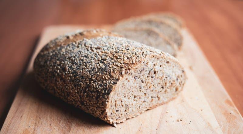 Gesneden multigrain eigengemaakt brood op een houten scherpe raad thuis stock foto