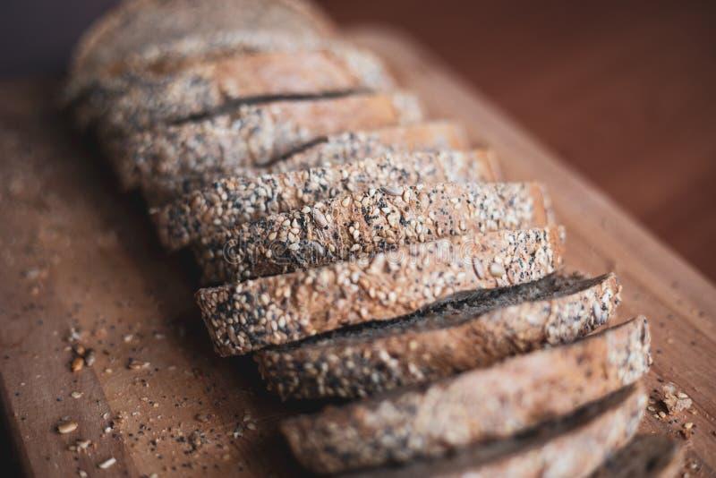 Gesneden multigrain eigengemaakt brood op een houten scherpe raad thuis royalty-vrije stock afbeeldingen