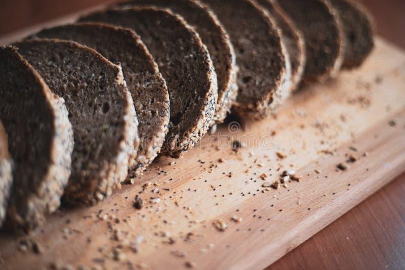 Gesneden multigrain eigengemaakt brood op een houten scherpe raad thuis royalty-vrije stock foto