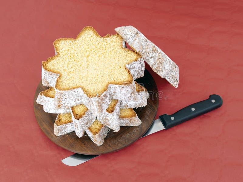 Gesneden pandoro, Italiaans zoet gistbrood, traditionele Kerstmis behandelt Met mes op rood Boven leg vlak mening royalty-vrije stock afbeeldingen
