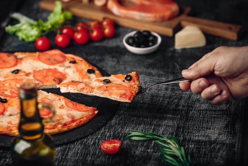 Gesneden plak van pizza ter beschikking met kaas, forel, tomaten, olijven en garnalen op schoolbord stock foto