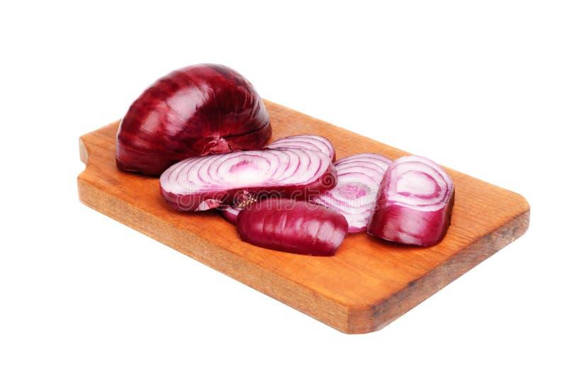 Gesneden purpere uien op scherpe raad stock fotografie