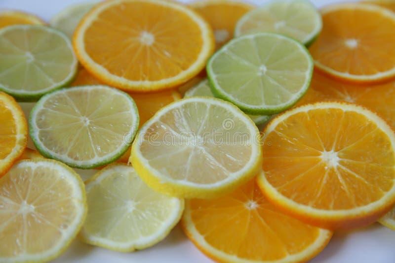 Gesneden ringen van sinaasappel en citroen, en kalk die op witte achtergrond wordt geïsoleerd stock foto's