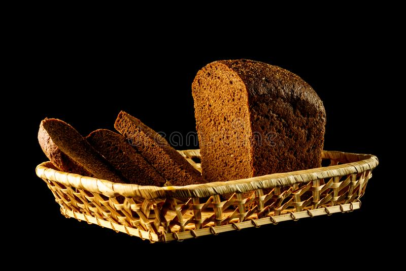 Gesneden roggebrood in een mand op een zwarte achtergrond Een brood van vers roggebrood met plakken die op een zwarte achtergrond royalty-vrije stock foto