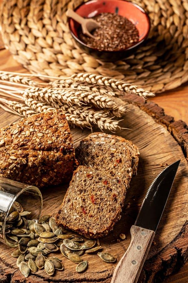 Gesneden roggebrood op scherpe raad Het gehele brood van de Korrelrogge met zaden Hoogste mening stock fotografie