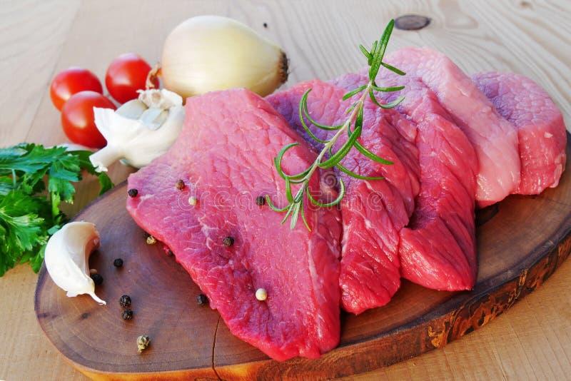 Gesneden rood vlees op houten raad met kruiden en kruiden stock afbeeldingen