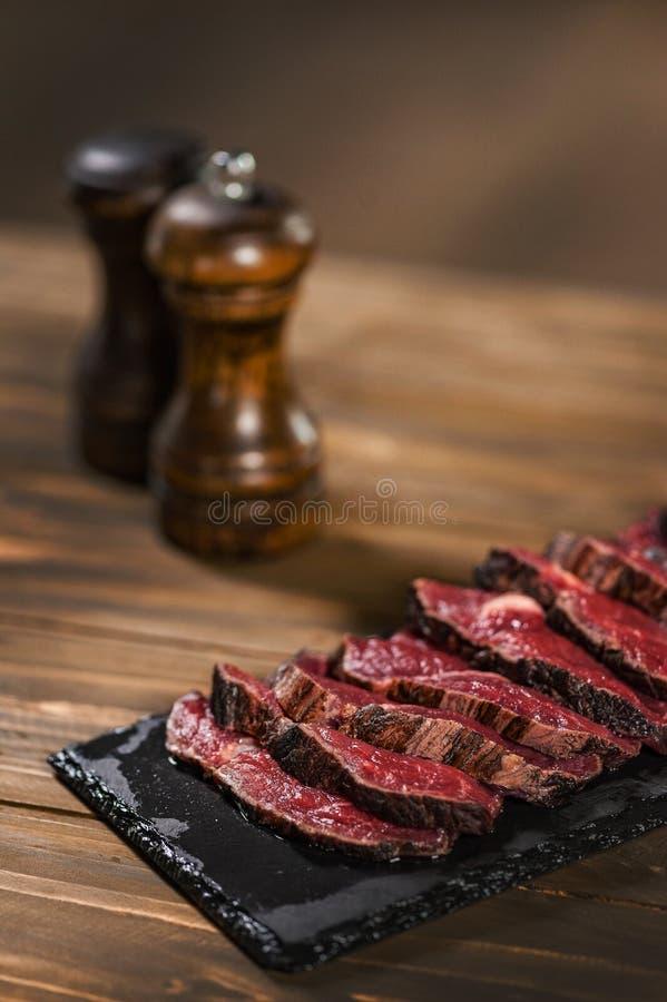 Gesneden rundvlees Dichtbij zijn zoute en peperschudbeker royalty-vrije stock fotografie