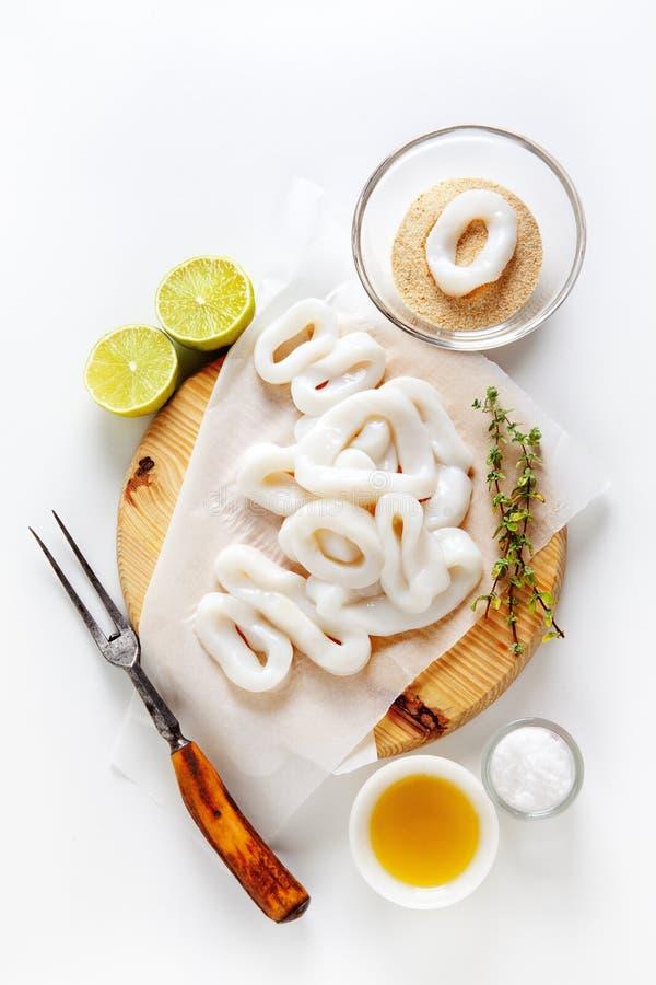 Gesneden ruwe pijlinktvisringen met kalk, olijfolie, broodkruimels Prepar stock fotografie