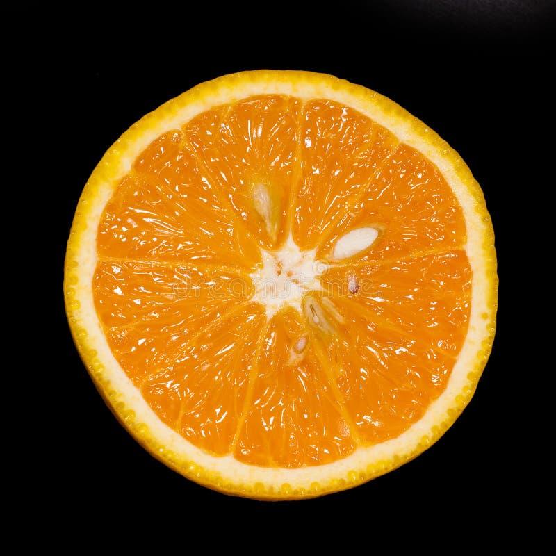 Gesneden sinaasappel die op zwarte wordt geïsoleerd stock afbeeldingen