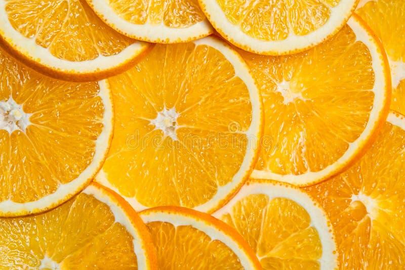 Gesneden sinaasappelenachtergrond, helder vers die fruit in zelfs plakken wordt gesneden royalty-vrije stock foto