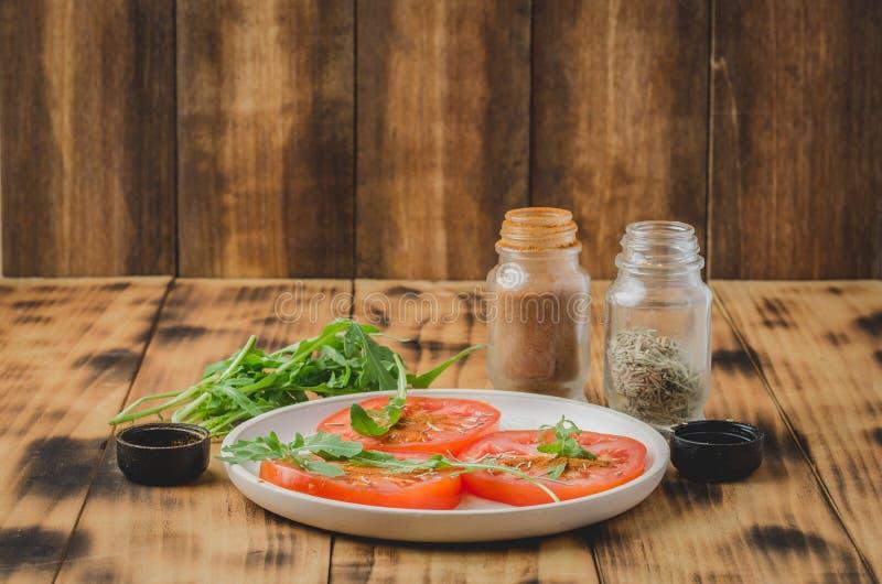 gesneden tomaten en van arugulakruiden salade In een witte kom op een houten lijst Selectieve nadruk stock fotografie