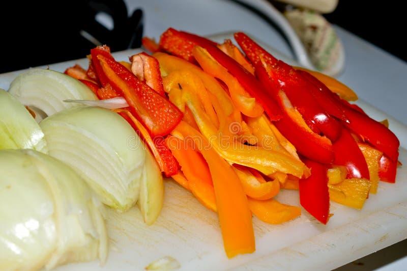 Gesneden uiengroene paprika's stock afbeeldingen