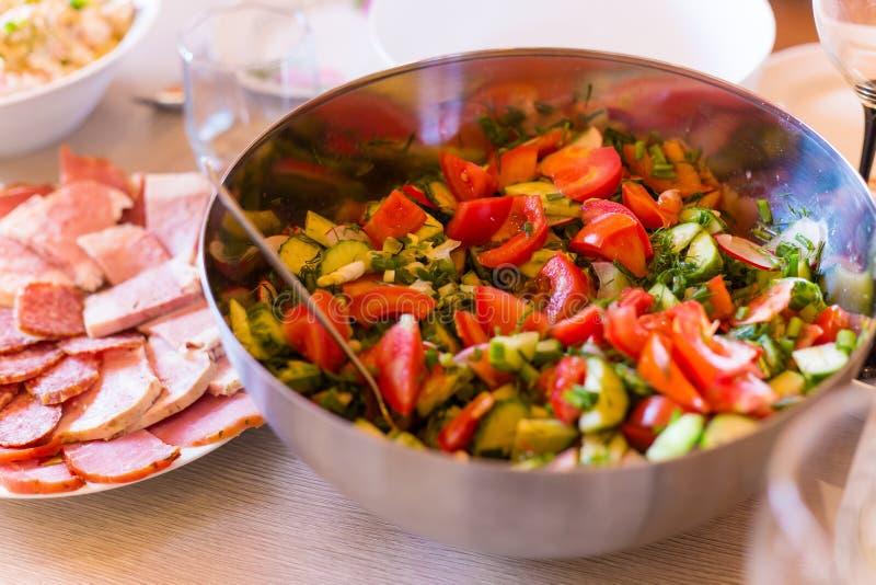 Gesneden verse groentesalade van tomaten, komkommers en groene uien met olijfolie stock foto
