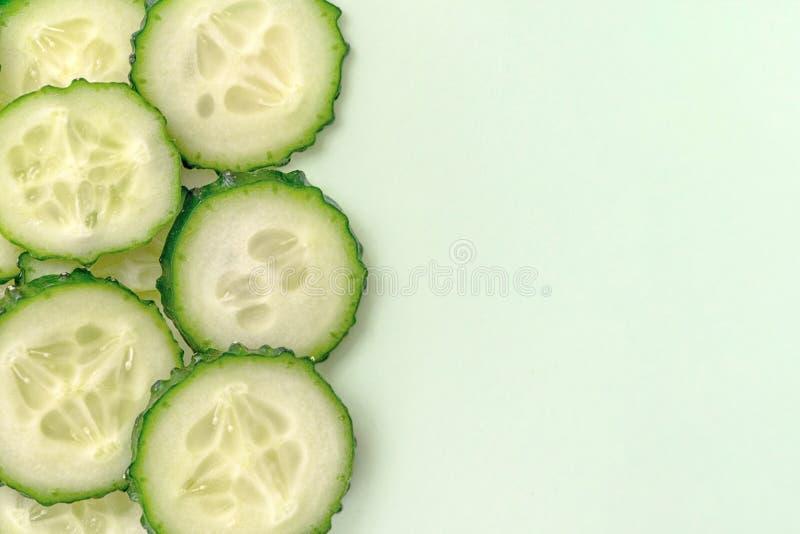 Gesneden verse komkommer op lichtgroene achtergrond Sluit omhoog, hoogste mening Met exemplaarruimte stock afbeelding