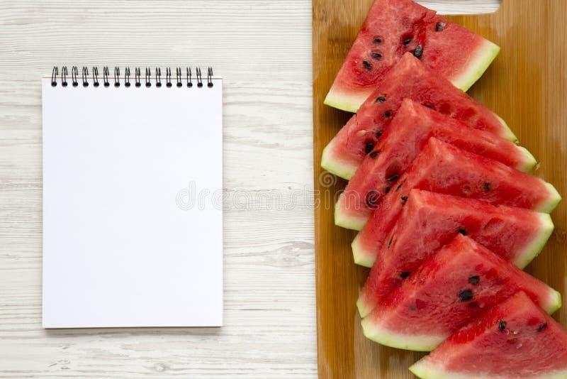 Gesneden verse rijpe watermeloen op scherpe bamboeraad met leeg notitieboekje over witte houten achtergrond, hoogste mening stock foto