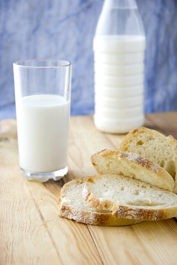 Gesneden wit brood †‹â€ ‹, een glas melk en een fles op de achtergrond royalty-vrije stock afbeeldingen