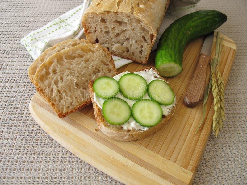 Gesneden wit brood met roomkaas en komkommer stock afbeeldingen