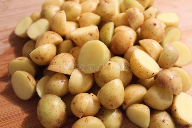 Gesneden witte die aardappels in de helft op scherpe raad worden gesneden stock fotografie
