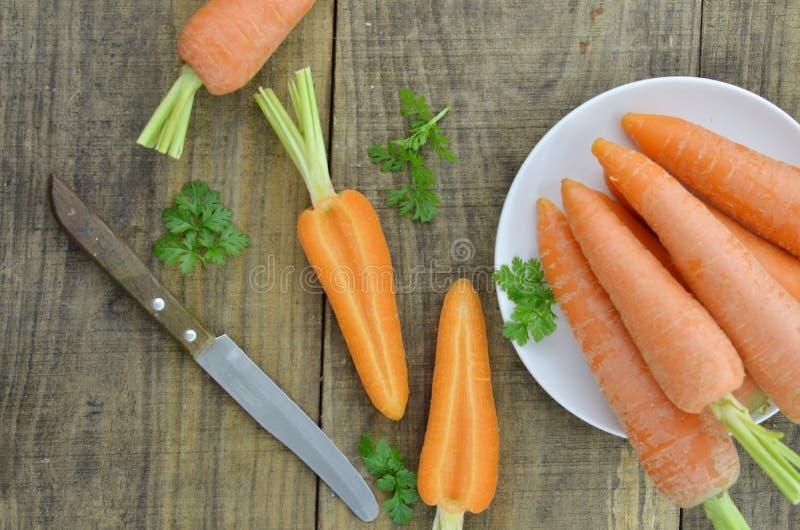Gesneden wortel en Witte plaat met verse wortel op houten royalty-vrije stock foto's