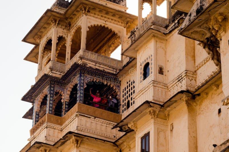 Gesneden zandsteen buitenmuren van het udaipurpaleis met bogen, balkon en vensters royalty-vrije stock foto's