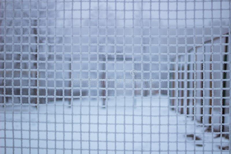 Gesneeuwde sportwerf achter ijzig metaal netto in de wintertijd stock fotografie