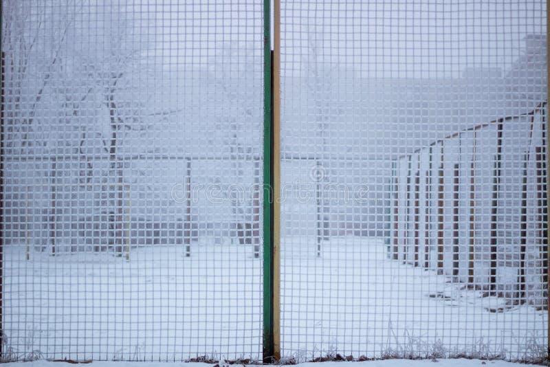 Gesneeuwde sportwerf achter ijzig metaalnet in de winter stock foto's