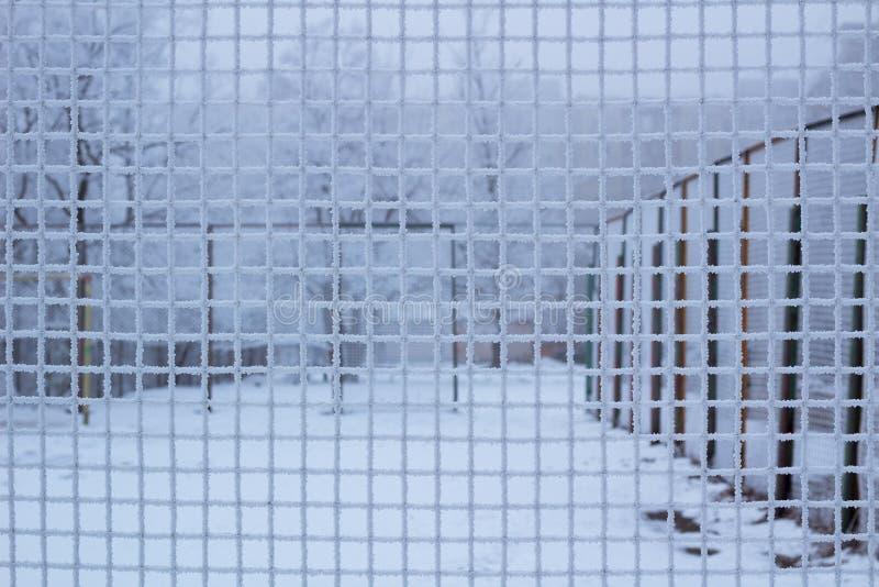 Gesneeuwde sportyard achter ijzig metaalnet netto in de winter stock afbeelding