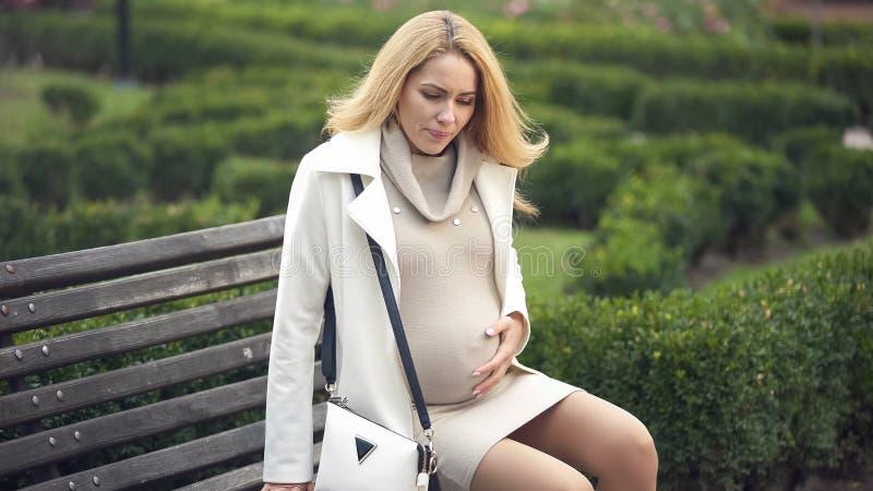 Gesorgt störte die Erwartung von Dame, die ihren Bauch, sitzend auf der Bank berührt, schauend lizenzfreie stockbilder