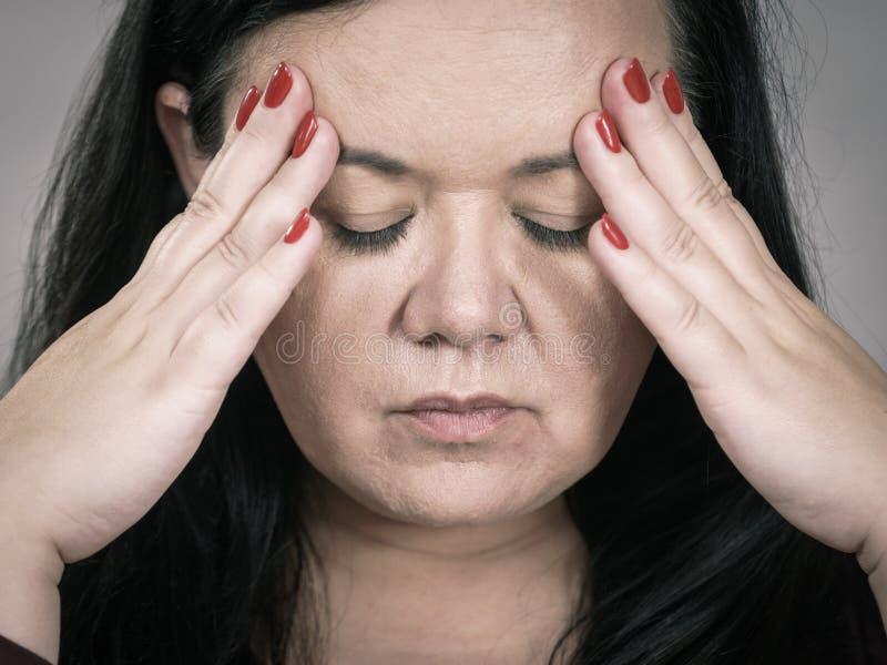 Gesorgte Frau, die painfull Kopfschmerzen hat stockfoto