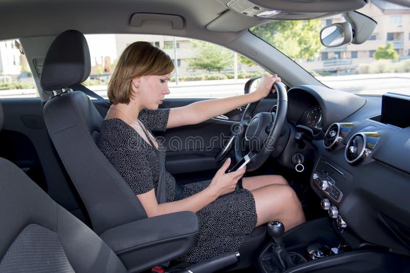 Gesorgte und betonte Frau, die Auto fährt, während das Simsen am Handy ablenkte lizenzfreie stockbilder