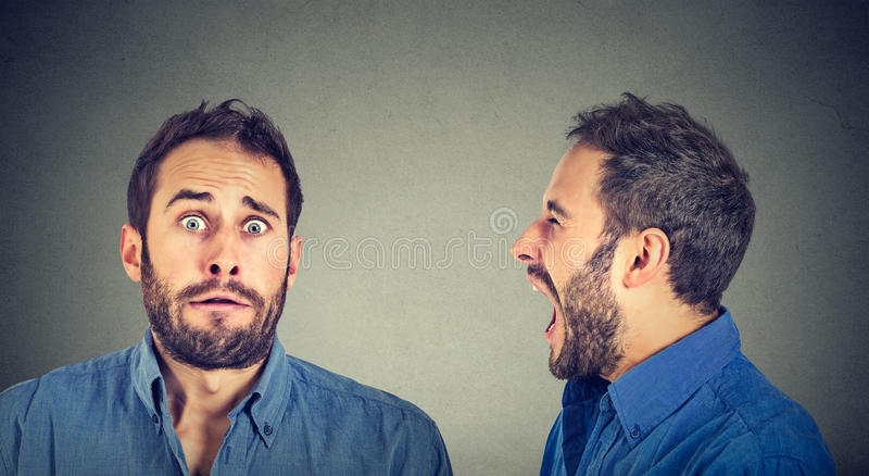 Gespaltene Persönlichkeit Verärgerter Mann, der an erschrocken schreit lizenzfreies stockbild