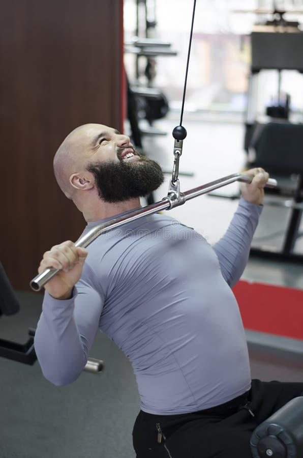 Gespannen jonge mens die in de gymnastiek, sportenoefeningen voor het gezonde leven uitwerken royalty-vrije stock foto